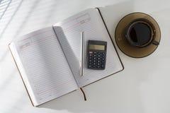 Auf dem Tisch in einem offenen Tagebuch und in einem Stift mit einem Taschenrechner, stehend nahe bei einem Tasse Kaffee Lizenzfreie Stockbilder