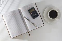 Auf dem Tisch in einem offenen Tagebuch und in einem Stift mit einem Taschenrechner, stehend nahe bei einem Tasse Kaffee Lizenzfreie Stockfotos