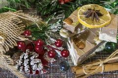 Auf dem Tisch gelegte Weihnachtsdekorationen Kuchen, Zimt, Sternanis, Stücke getrocknete Zitronen, Kiefernniederlassung lizenzfreie stockfotografie