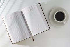 Auf dem Tisch nahe bei dem offenen Blog ist ein Tasse Kaffee Stockbilder