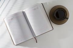 Auf dem Tisch nahe bei dem offenen Blog ist ein Tasse Kaffee Stockbild