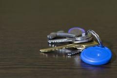 Auf dem Tisch vom dunklen Holz ist ein Schlüsselbund zum Haus und zum Auto lizenzfreies stockbild