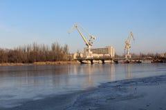 Auf den Banken des Flusses sind große Kräne Diese Anlage errichtet Schiffe Lizenzfreie Stockbilder