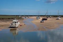 Auf den Strand gesetzte Boote bei Ebbe in der Nord-Norfolk-Küstenstadt Stockbilder