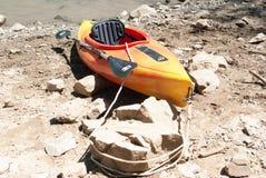 Auf den Strand gesetzter Kajak gebunden an einem Felsen Stockfotos