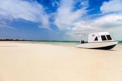 Auf den Strand gesetztes Boot in der tropischen Bucht Lizenzfreie Stockfotografie