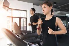 Auf den Tretmühlen, aktiver junger Frau und dem Mann laufen, die auf Tretmühle in der Turnhalle läuft stockfotografie