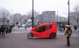 Auf den ursprünglichen roten Fahrradfahrten des Bürgersteigs Bürger gehen Lizenzfreie Stockfotografie