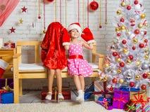 Auf der Bank sitzt ein Mädchen in einer Kappe und Handschuhe von Santa Claus, das andere Mädchen trugen eine Tasche auf seinem Ko Lizenzfreies Stockbild