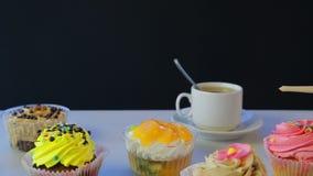 Auf der grauen Tabelle ist Tee in einer weißen Schale und in den Kuchen stock video