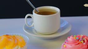 Auf der grauen Tabelle ist Tee in einer weißen Schale und in den Kuchen stock footage