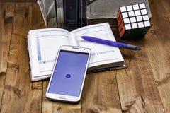 Auf der Holzoberfläche sind Bücher, ein Notizbuch mit einem Stift, ein Würfel Rubik und ein Smartphone Stockfoto