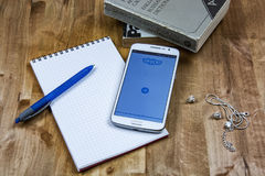 Auf der Holzoberfläche sind Bücher, ein Notizbuch mit einem Stift, eine Kette und ein Smartphone Stockfotografie
