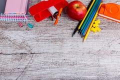 Auf der Holzoberfläche sind Notizblöcke, bunte Bleistifte, ein Hefter und ein Spielzeugflugzeug Platz für die Aufschrift Lizenzfreie Stockfotos
