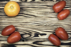 Auf der Holzoberfläche sind rote und gelbe Tomaten Lizenzfreies Stockbild