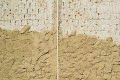 Auf der neuen Backsteinmauer ist ein neuer Gips angewandt Die alte Wand Beschaffenheit und Hintergrund Stockbilder