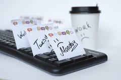 Auf der schwarzen Tastatur viele Aufkleber mit den Namen der Wochentage nahe bei einem Papiertasse kaffee mit der Aufschrift stockfoto