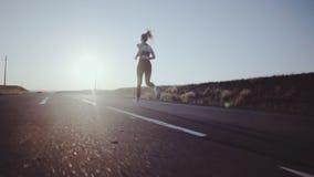 Auf der sonnenbeschienen Straße mit den Markierungen, die sportliches Mädchen laufen lassen stock footage