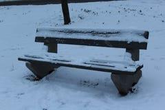 Auf der Straße gibt es eine alte Bank Er wird mit Schnee abgedeckt Winter Frost auf der Straße Stockfotografie