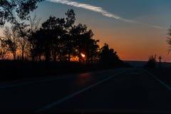 Auf der Stra?e mit der sch?nen Ansicht des Sonnenuntergangs umgebend durch B?ume stockbilder