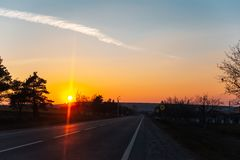 Auf der Stra?e mit der sch?nen Ansicht des Sonnenuntergangs umgebend durch B?ume lizenzfreie stockfotografie