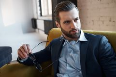 Auf der Suche nach Inspiration Durchdachter hübscher Geschäftsmann hält Gläser und denkt an Zukunft lizenzfreie stockfotos