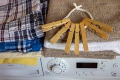 Auf der Waschmaschine sind saubere Tücher, Wäscheklammern und deterg Stockfoto
