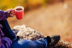 Auf ein Bergmädchen, das einen Becher Tee hält Stockfoto