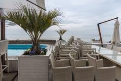 Auf einander geflochtene Stühle angehäuft nahe dem Pool auf Seepromenade Stockfotos