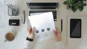 Auf eine menschliche Hand der weißen Tabelle, die ein Papier mit Diagrammen hält stock video footage