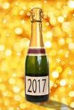 2017 auf einem Aufkleber einer Flasche von Champagne, glänzender goldener Hintergrund, Konzept des neuen Jahres Stockfotografie
