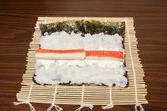 Auf einem Bambus-Mat Nori-Blatt mit Reis, haften Käse und Krabbe Stockfotos