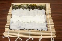 Auf einem Bambus-Mat Nori-Blatt mit Reis, Käse Stockfotos