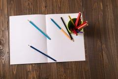 Auf einem Blatt sind Bleistifte mit einem Glas Lizenzfreies Stockbild