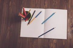 Auf einem Blatt sind Bleistifte mit einem Glas Stockfotos