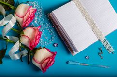 Auf einem blauen Hintergrund gibt es drei Rosen, geöffnetes leeres Notizbuch stockbilder