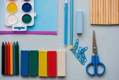 Auf einem blauen Hintergrund, Schulzubehör und einem Stift farbige Bleistifte, ein Zirkel, ein Zirkel, eine Schere, Lizenzfreies Stockbild