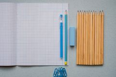 Auf einem blauen Hintergrund, Schulzubehör und einem Stift farbige Bleistifte, ein Zirkel, ein Zirkel, eine Schere, Lizenzfreie Stockfotos