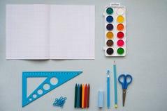 Auf einem blauen Hintergrund, Schulzubehör und einem Stift farbige Bleistifte, ein Zirkel, ein Zirkel, ein Paar von Stockfotografie