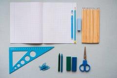 Auf einem blauen Hintergrund, Schulzubehör und einem Stift farbige Bleistifte, ein Zirkel, ein Zirkel, ein Paar von Lizenzfreie Stockbilder