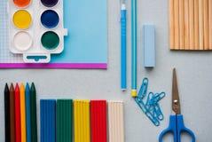 Auf einem blauen Hintergrund, Schulzubehör und einem Stift farbige Bleistifte, ein Zirkel, ein Zirkel, ein Paar von Stockfotos