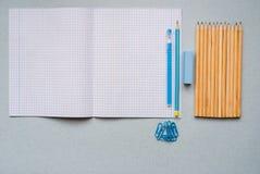 Auf einem blauen Hintergrund, Schulzubehör und einem Stift farbige Bleistifte, ein Zirkel, ein Zirkel, ein Paar von Stockbild