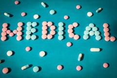 Auf einem blauen Hintergrund wird das Wort, das von den Tabletten medizinisch ist, ausgebreitet Konzeptmedizin Lizenzfreies Stockfoto