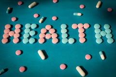 Auf einem blauen Hintergrund wird die Wortgesundheit von den Tabletten ausgebreitet Konzeptmedizin, medizinisch Stockbilder