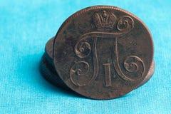 Auf einem blauen Stoffhintergrund gibt es eine alte russische Münze des 17. Jahrhunderts, alle Details sind sichtbar Stockbild