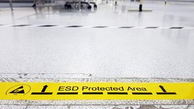 Auf einem Boden der Elektronik bedeckte die Herstellung industrielles Linoleum klebt ein gelbes Band mit einem warnenden Standard stockbild