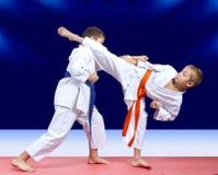 Auf einem dunkelblauen Hintergrund zwei bilden Athleten Durchschlagshand aus und brennen Bein durch, um sich zu treffen stockbilder