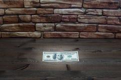 Auf einem dunklen Holztisch nahe einer Backsteinmauer einer Rechnung beleuchteten hundert Dollar durch einen Strahl des Lichtes Stockbild
