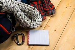 Auf einem hölzernen hellen Hintergrund gibt es ein Stück des Weißbuches für das Schreiben, des touristischen Satzes des Seils, de Stockbild