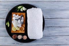 Auf einem hölzernen Hintergrund ist ein rundes Brett mit Sachen für die Badekurort- und Aromaverfahren lizenzfreie stockfotografie